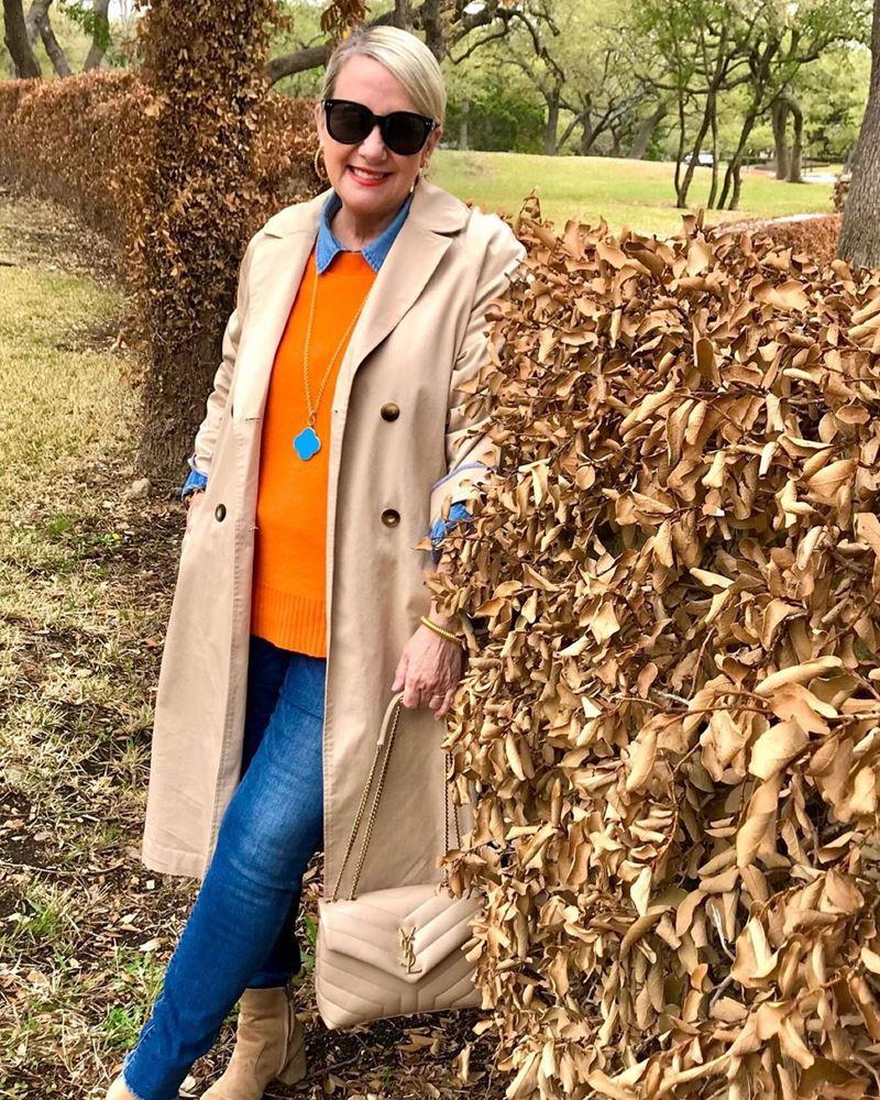 Стиль 60+ наряды от американки Кимберли - Оранжевый свитер на голубую рубашку с джинсами и бежевым плащом