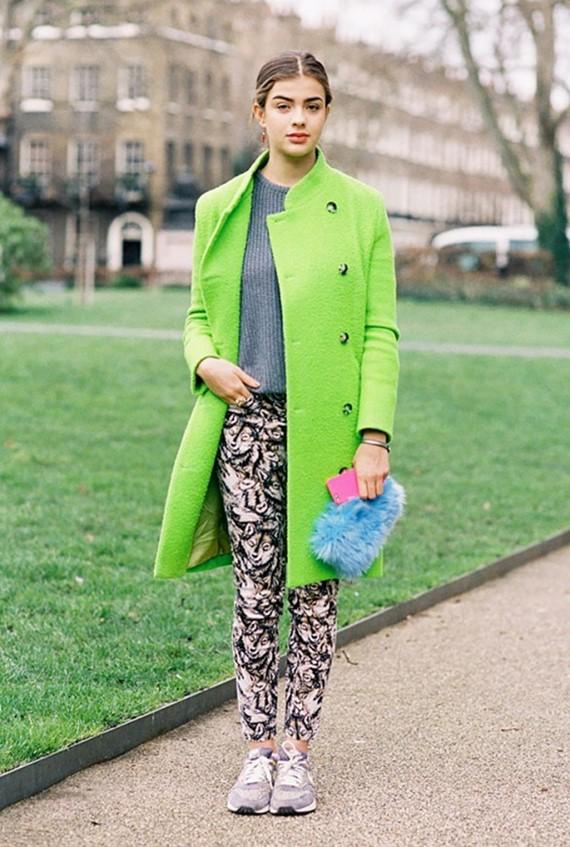 яркое салатовое пальто с брюками с принтом и кроссовками