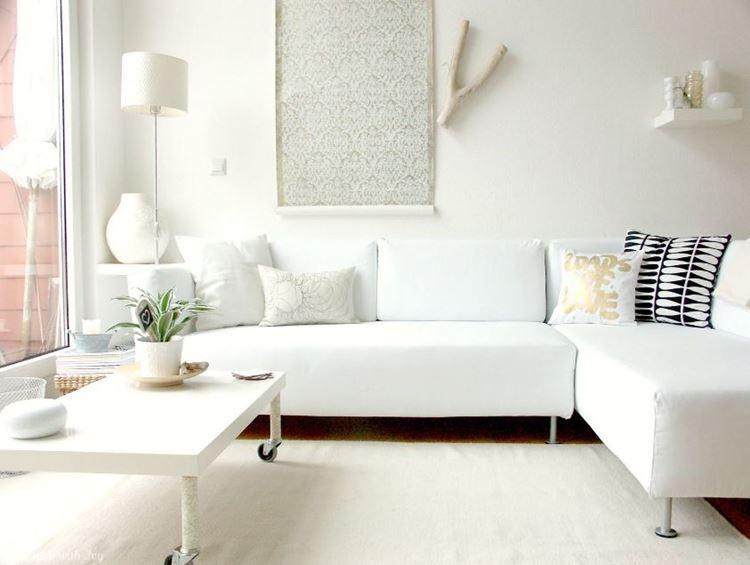 Белый диван в интерьере: монохромная белая комната с угловым диваном, кофейным столиком и аксессуарами