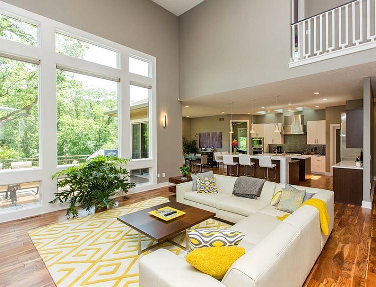 Бежевый диван в интерьере: угловой кожаный с серыми и желтыми подушками в гостиной с бежевыми стенами