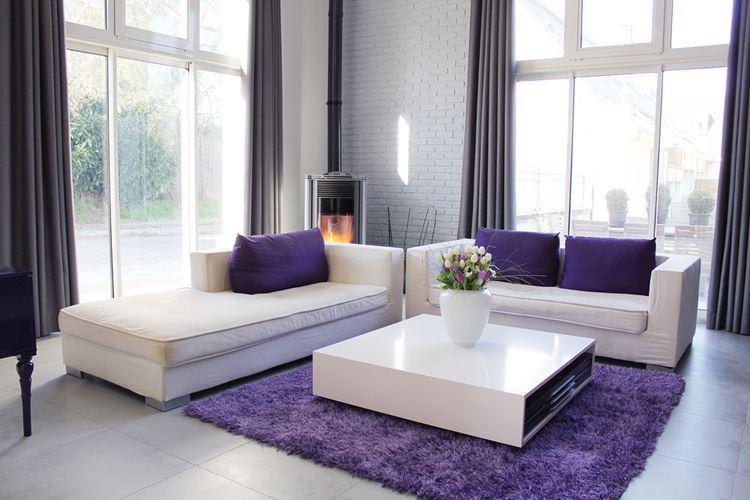 Бежевый диван в интерьере: гостиная с белыми кирпичными стенами и диваны с тёмно-фиолетовыми подушками и ковром