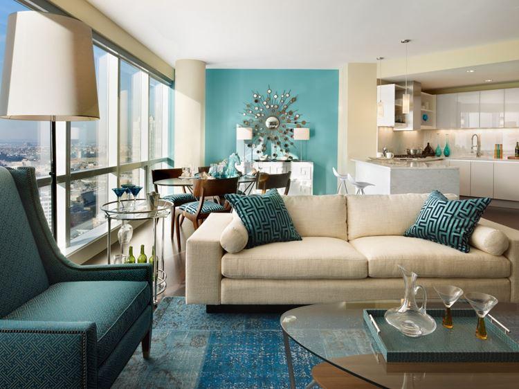 Бежевый диван в интерьере: бирюзовое кресло, стена и подушки