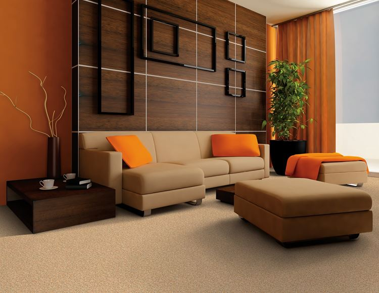 Бежевый диван в интерьере: деревянная стена, оранжевые аксессуары и бежевый ковер