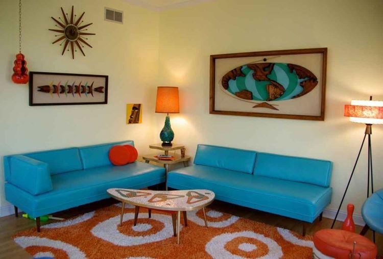 Бирюзовый диван в интерьере: два ярких кожаных сине-бирюзовых оттенка с оранжевым ковром и жёлтыми стенами