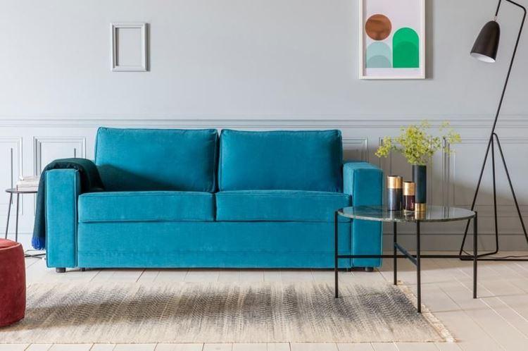 Бирюзовый диван в интерьере: яркий двухместный бархатный диван в гостиной со светло-серыми стенами