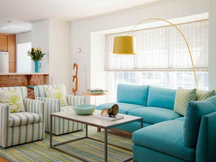 Бирюзовый диван в интерьере: угловой диван в комнате с белыми стенами и двумя креслами в бело-зеленую полоску