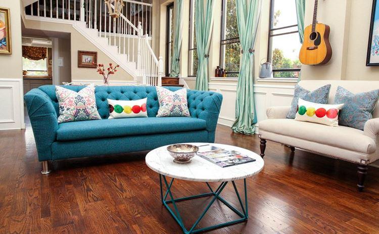 Бирюзовый диван в интерьере: гостиная с диваном-барокко, пола из тёмного дерева и мятными шторами