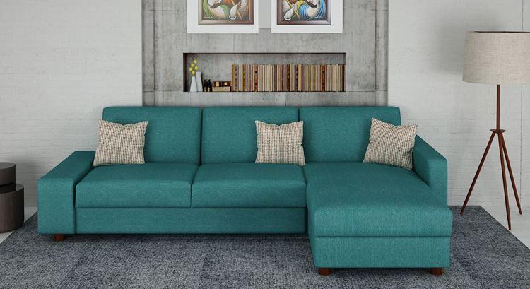 Бирюзовый диван в интерьере: диван оттенка морской волны со светлыми подушками в серой гостиной