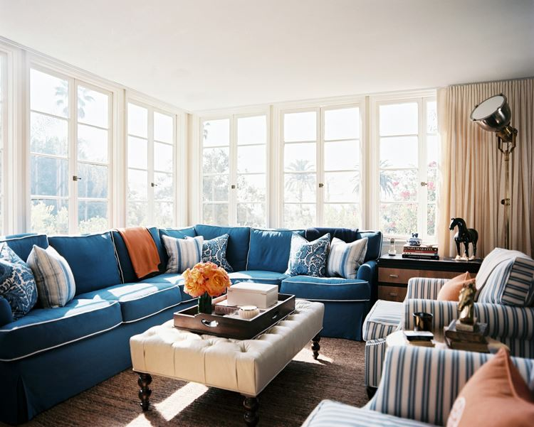 Голубой диван в интерьере: большой угловой диван с подушками в светлой комнате с большими окнами
