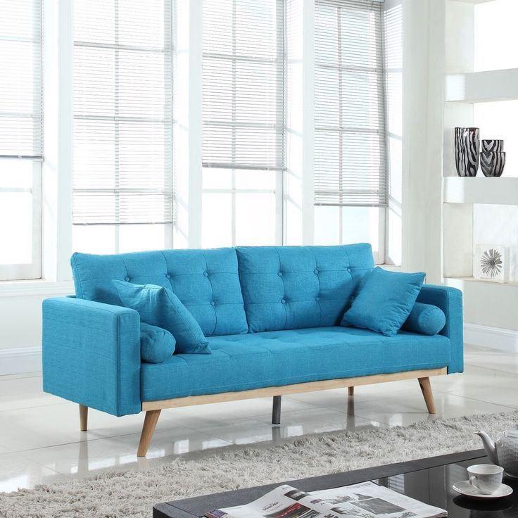 Голубой диван в интерьере: диван с подушками и на деревянных ножках в гостиной с белыми стенами и серым ковром