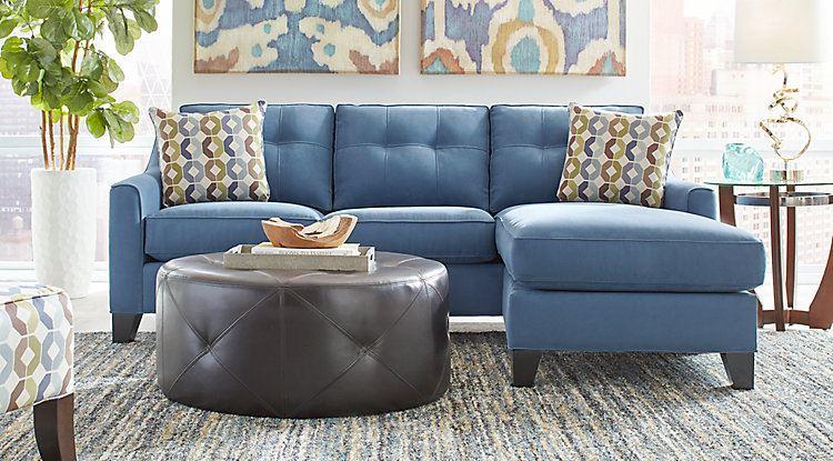 Голубой диван в интерьере: трёхместный диван  с подушками с принтом и кожаным пуфом-столиком