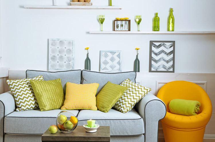Голубой диван в интерьере: двухместный мягкий диван с яркими жёлтыми и зелёными подушками
