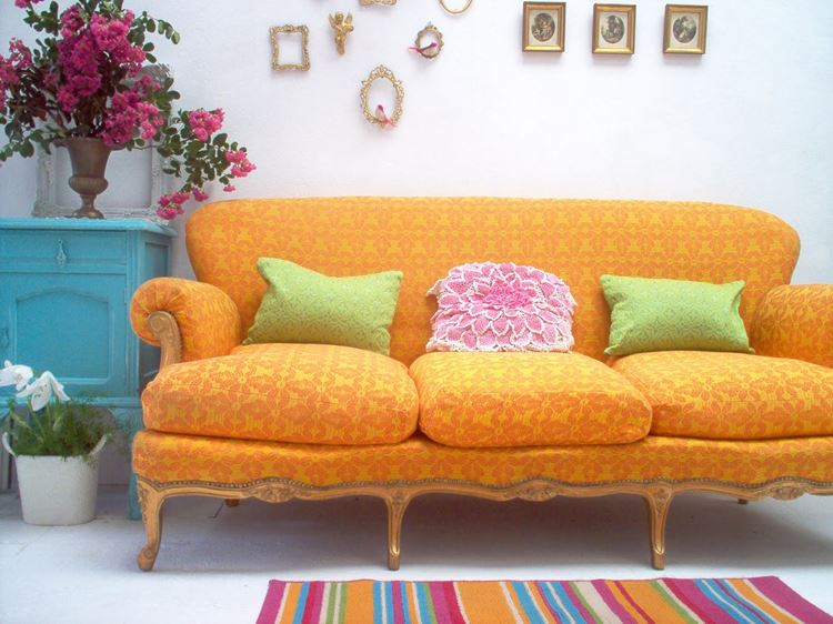 Оранжевый диван в интерьере: жёлто-оранжевый диван с принтом и подушками