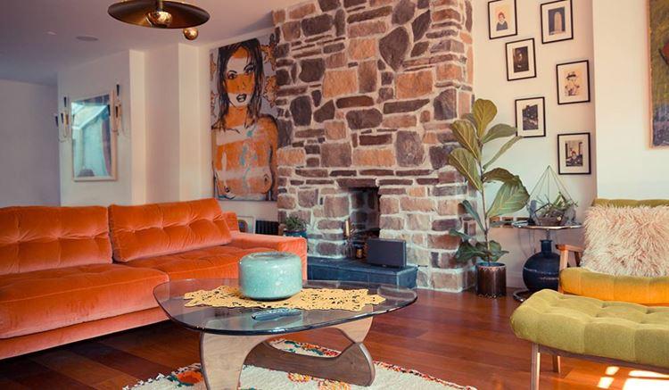 Оранжевый диван в интерьере: комната с кирпичной стеной и бархатным диваном