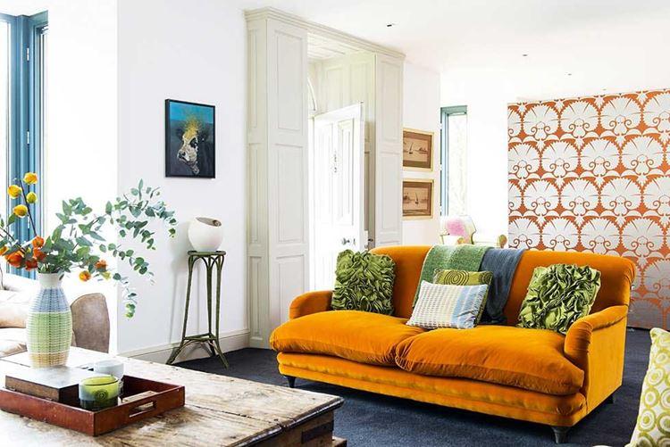 Оранжевый диван в интерьере: бархатный диван рыже-оранжевого оттенка с зелёными подушками