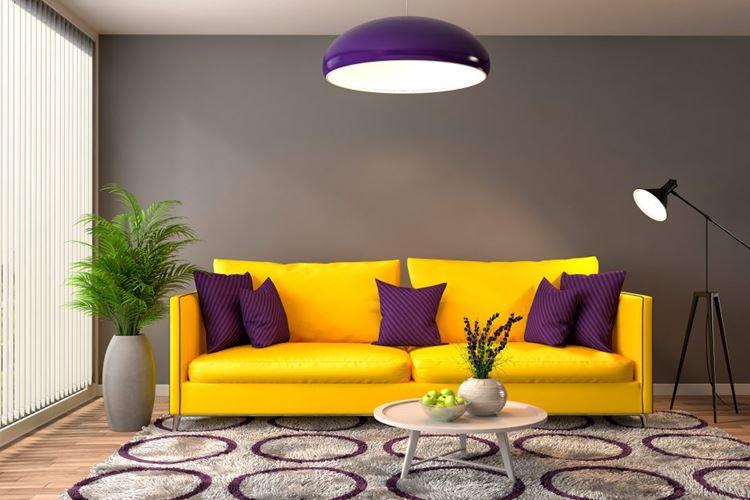 Жёлтый диван в интерьере: яркий диван с тёмными фиолетовыми подушками с бежевой гостиной