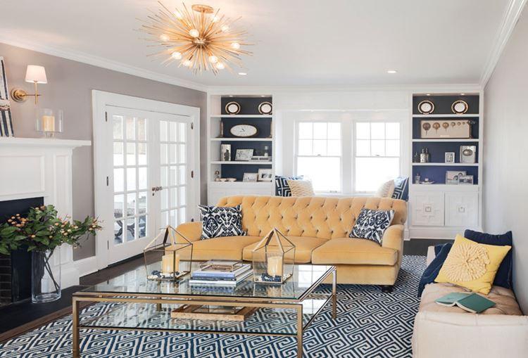 Жёлтый диван в интерьере: диван мягкого ванильного оттенка с бело-синими подушками с принтом
