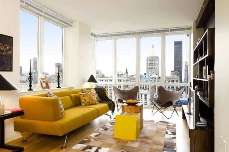 Жёлтый диван в интерьере: гостиная с большими окнами и жёлтым диваном в стиле конструктивизм