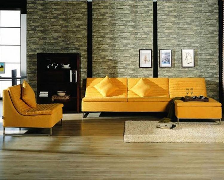 Жёлтый диван в интерьере: гостиная с кирпичной стеной в тёплых зелёных оттенках