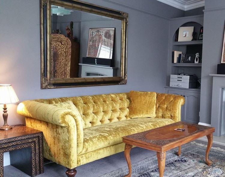 Жёлтый диван в интерьере: гостиная со старинным вельветовым жёлтым диваном и деревянным столиком