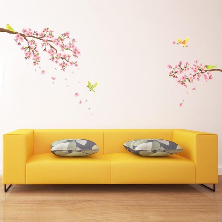 Жёлтый диван в интерьере: минималистичный диван на фоне бледно-розовых цветочных обоев