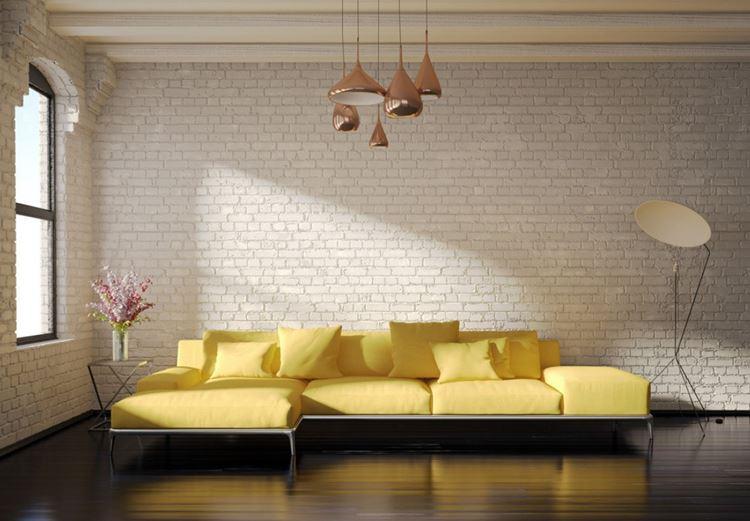 Жёлтый диван в интерьере: гостиная в стиле лофт с кирпичной стеной и жёлтым угловым диваном с подушками