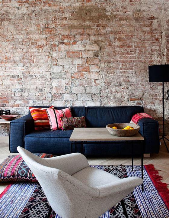 Джинсовый диван - интерьер в стиле лофт с кирпичной стеной и восточными коврами и подушками