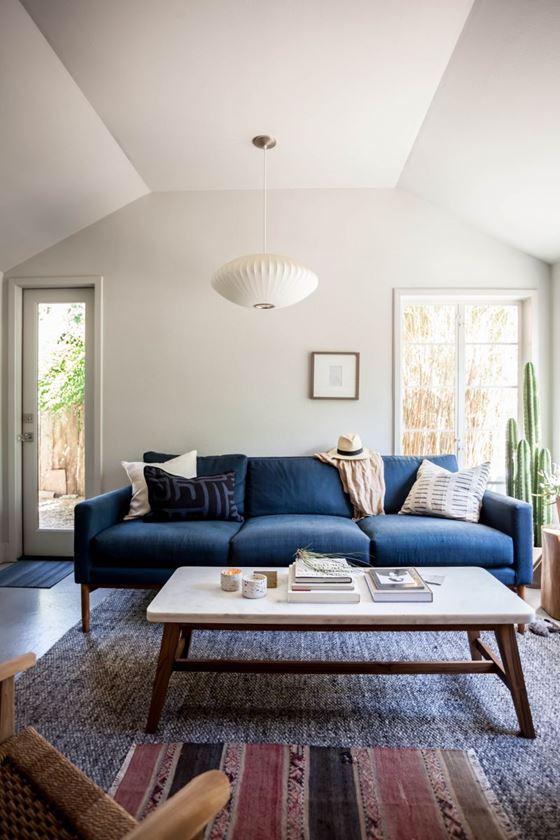 Джинсовый диван - трехместный с подушками в гостиной с белыми стенами