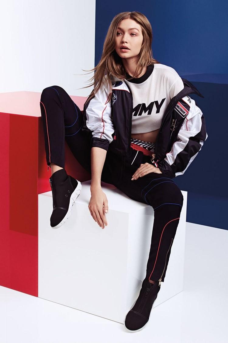 Джиджи Хадид в лукбуке Tommy X Gigi весна-лето 2018 - Чёрные брюки скинни, чёрно-белая спортивная куртка, белый кроп-топ и чёрные кеды с белой подошвой